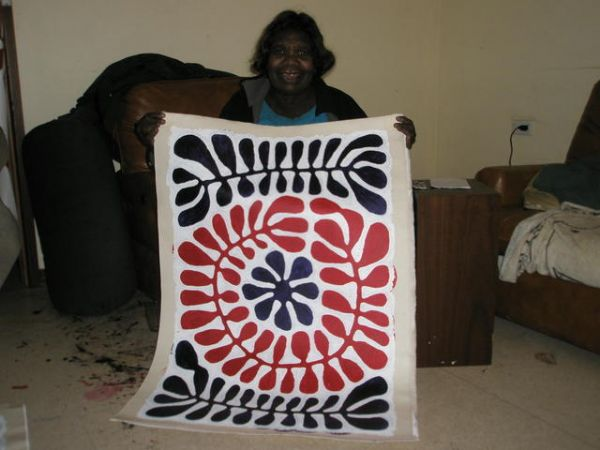 """Classic Aboriginal Art : Mitjili Naparrula holding her painting titled """"Watiya Tjuta"""" (90x60cm). This highly-collectible Aboriginal artist is internationally exhibited. When Mitjili began painting at the Ikuntji Women's Centre in 1993, her main influence was the style of the Papunya Tula artists. The purchase of this artwork also includes a Certificate of Authenticity and the original photograph of the artist holding this painting of hers."""